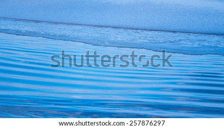 Very smooth and calm waves over sand reflecting the blue sky in peaceful seascape scene - stock photo