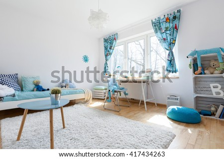 Very spacious and light child room with large window, filled with white and blue decorative elements - stock photo