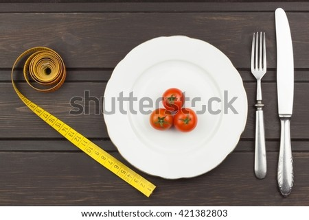 Very strict diet. Dietary vegetable diet. Tomatoes on a plate. Slimming diet. White plate with tomato on dark table.  - stock photo
