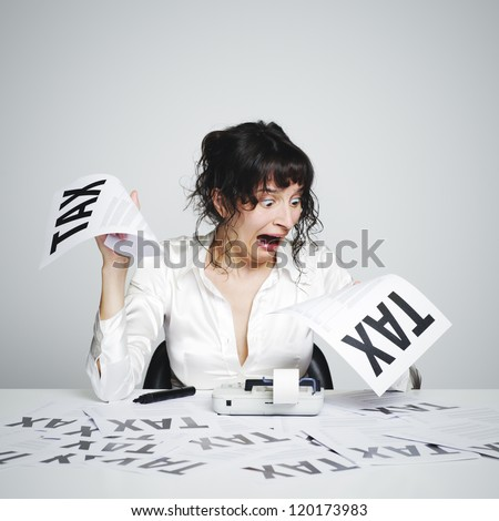 Very surprised  woman at her desk looking at terrible tax bills - stock photo