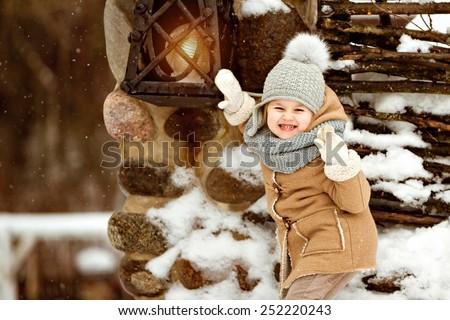 Very sweet beautiful little girl child in a beige coat crusade amid rustic winter near the lantern - stock photo