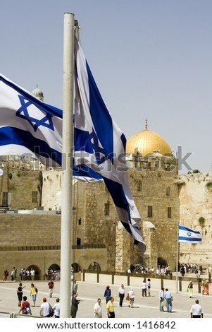 Very symbolic picture of Jerusalem. Israeli flags, the western wall, and the golden dome mosque - stock photo