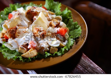 Very tasty and appetizing salad with chicken meat quail eggs and toasts. - stock photo