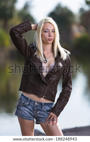 Very thin blonde model posing outdoors in jeans shorts and leather brown jacket - stock photo