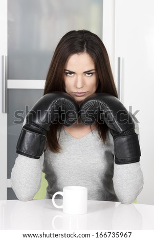 very tired looking woman early in the morning drinking a cup of coffee - stock photo