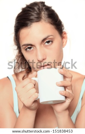 very tired looking woman early in the morning drinking a cup of coffee - selective focus on white cup with copy space - isolated on white - stock photo