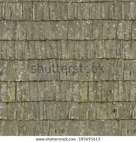 Very worn roof texture of wooden shingles with uneven edges and white spots. - stock photo