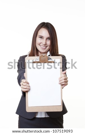 very young looking woman in a suit just starting out in business  holding up a clip board - stock photo