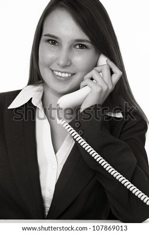 very young looking woman in a suit on the phone sitting at a desk - stock photo