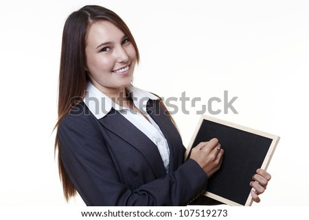 very young looking woman in a suit writing on a small back board - stock photo