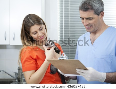 Vet Writing Prescription By Woman Holding Weasel - stock photo