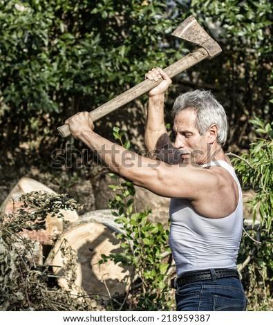 Veteran muscular woodcutter at work - stock photo