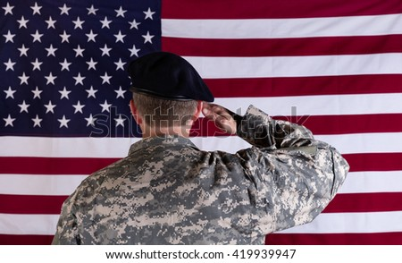 Veteran soldier, back to camera, saluting USA flag.  - stock photo
