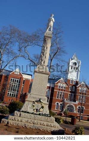 Veterans monument in city park.  Historic Donough Courthouse famous in several modern day movies.  Blue skies. - stock photo