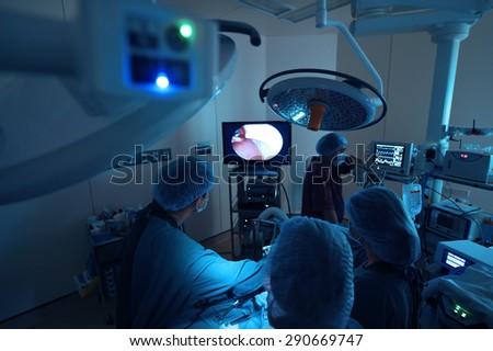 veterinarian doctor in operation room for laparoscopic surgical take with art lighting and blue filter  - stock photo