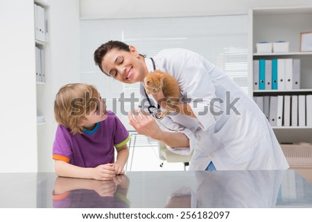 Veterinarian doing injection at a cat with its owner in medical office - stock photo