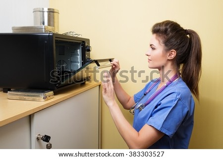 Veterinarian sterilizing medical instruments in special camera. - stock photo