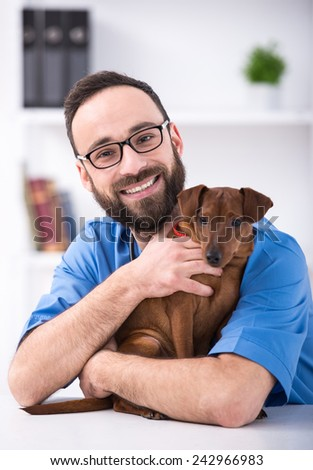 Veterinary clinic. Smiling male veterinarian is holding a dog. - stock photo