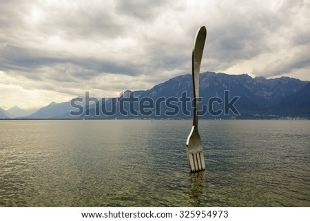 VEVEY, SWITZERLAND - SEPTEMBER 12, 2015: The Fork, 8m high statue made of stainless steel, embedded in the lake in February 1995 to commemorate the Alimentarium's tenth anniversary in Vevey - stock photo