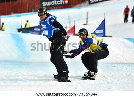 VEYSONNAZ, SWITZERLAND - JANUARY 22: Finalists Andrey Boldokov (RUS) + (l) Nick Baumgartner (USA) at finish FIS World Championship Snowboard Cross finals : January 22, 2012 in Veysonnaz Switzerland - stock photo