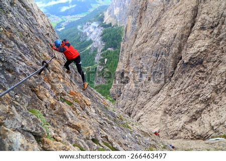 "Via ferrata ""Brigata Tridentina"" takes climber on steep walls high above the ground, Sella massif, Dolomite Alps, Italy - stock photo"