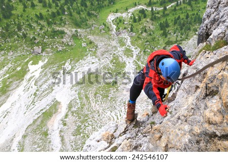 """Via ferrata climber gripping a hand hold while on """"Meisules"""" route, Sella massif, Dolomite Alps, Italy - stock photo"""