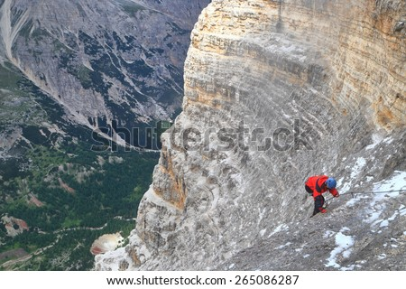 "Via ferrata ""Lipella"" and isolated woman climber on the rock wall, Tofana massif, Dolomite Alps, Italy - stock photo"