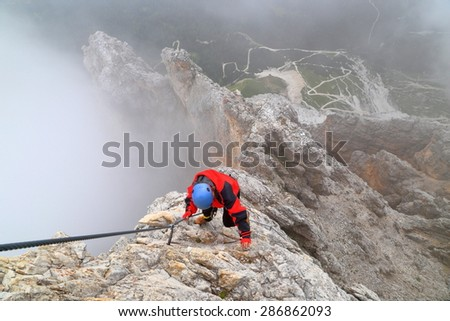 "Via ferrata ""Punta Ana"" and climber woman on vertical wall above the ground, Tofana massif, Dolomite Alps, Italy - stock photo"