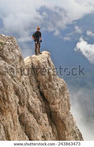 "Via ferrata ""Punta Ana"" with isolated climber on aerial ledge above the clouds, Tofana massif, Dolomite Alps, Italy - stock photo"