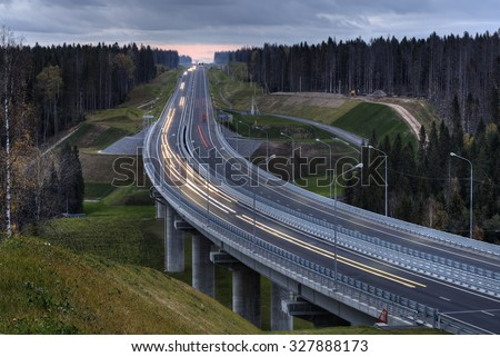 Viaduct overpass bridge on concrete pillars on the highway that crosses russian forest, early autumn night. - stock photo
