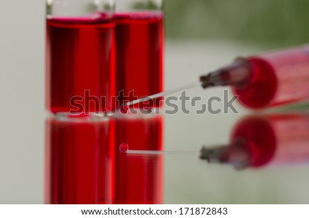 Vials and syringe on glass surface  - stock photo