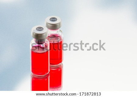 Vials of medicine against blue -white background  - stock photo