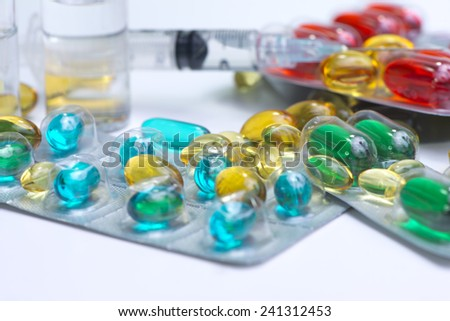 Vials with clear liquid, syringe and blister packs of multi-colored gelatin capsules. - stock photo