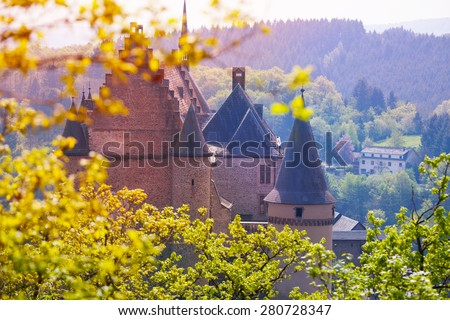 Vianden castle in Luxembourg through spring fresh leaves of the trees  - stock photo