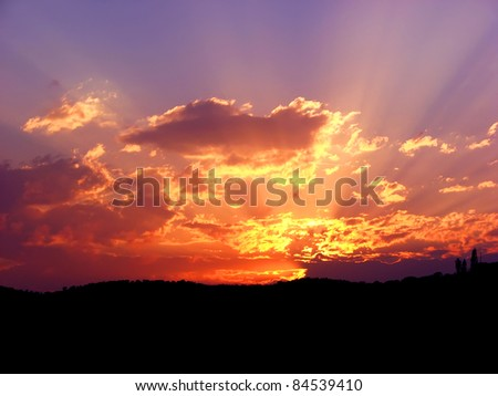 Vibrant and colorful purple sunset with silhouette of mountain - stock photo