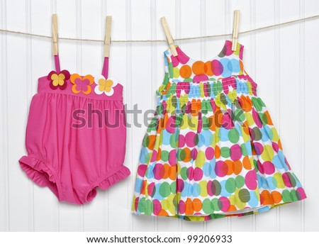 Vibrant Baby Dress and Bathing Suit on a Clothesline - stock photo