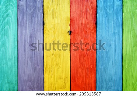 Vibrant, bright wooden fence with each plank a different colour. - stock photo
