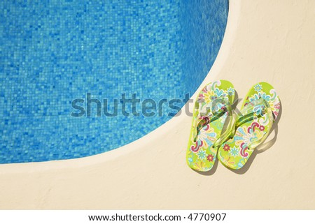 vibrant green flip-flops at the poolside - stock photo