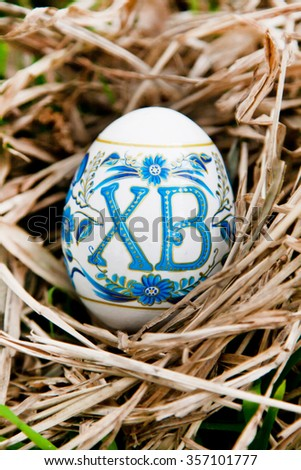 Vibrant holiday background with colorful Russian traditional Easter egg in the dry grass nest with copy space - stock photo