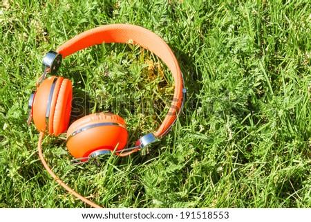 Vibrant orange wired headphones on the sunny grass - stock photo