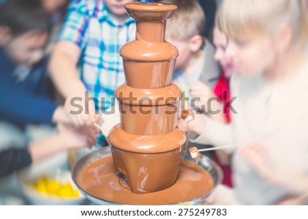 Vibrant Picture of Chocolate Fountain Fontain on childen kids birthday party with a kids playing around and marshmallows and fruits dip dipping into fountain  - stock photo