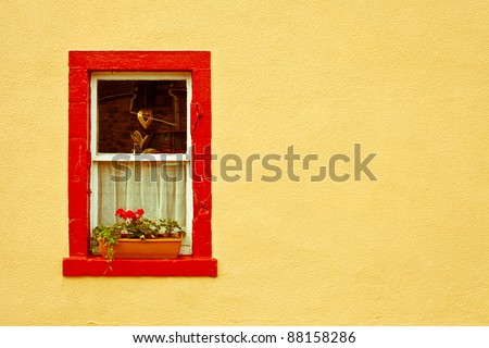 vibrant red window frame in a yellow wall - stock photo