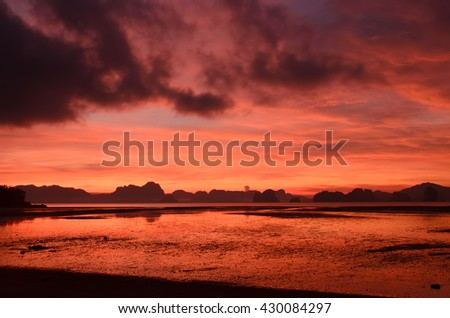 Vibrant sky with dark cloud in the early morning, low tide in tropical sea - stock photo