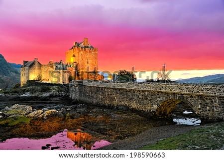 Vibrant sunset over the famous Eilean Donan Castle, Scotland - stock photo