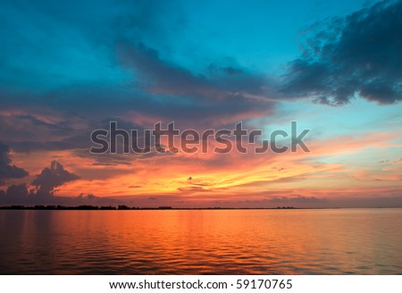 Vibrant sunset with clouds, blue sky background over water - stock photo