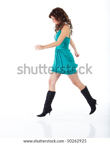 Vibrant young adult caucasian woman in a short turquoise dress with black boots and a brunette wig, shot on a white background. Not isolated. - stock photo
