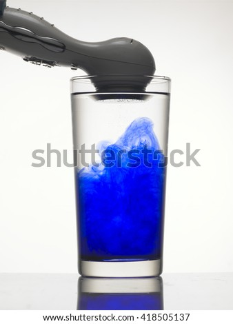 Vibration creates abstract form of blue color in glass of water.  - stock photo