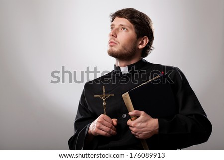 Vicar holding a holy bible and crucifix - stock photo