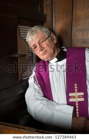 Vicar listening to the sins of a person in the confession booth - stock photo