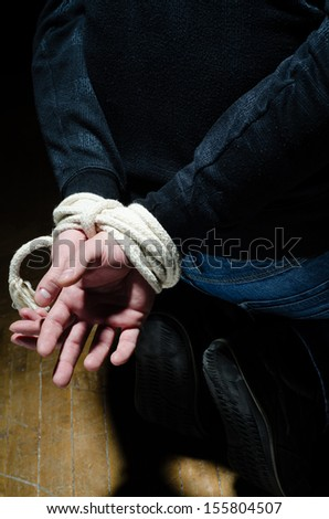 Victim male having his hands tight with a rope - stock photo